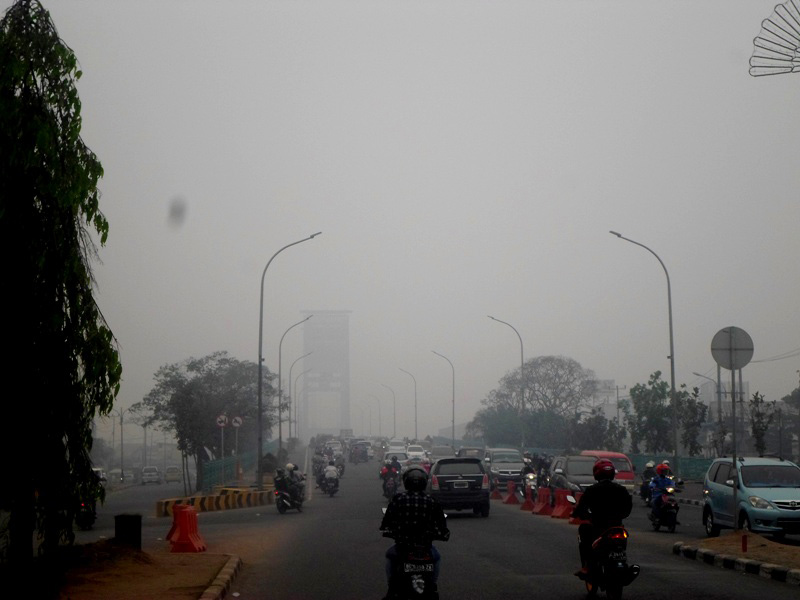 Meski tengah hari, Jembatan Ampera di Palembang nyaris tidak terlihat karena tertutup kabut asap, Senin, 26 Oktober 2015. Foto: Taufik Wijaya